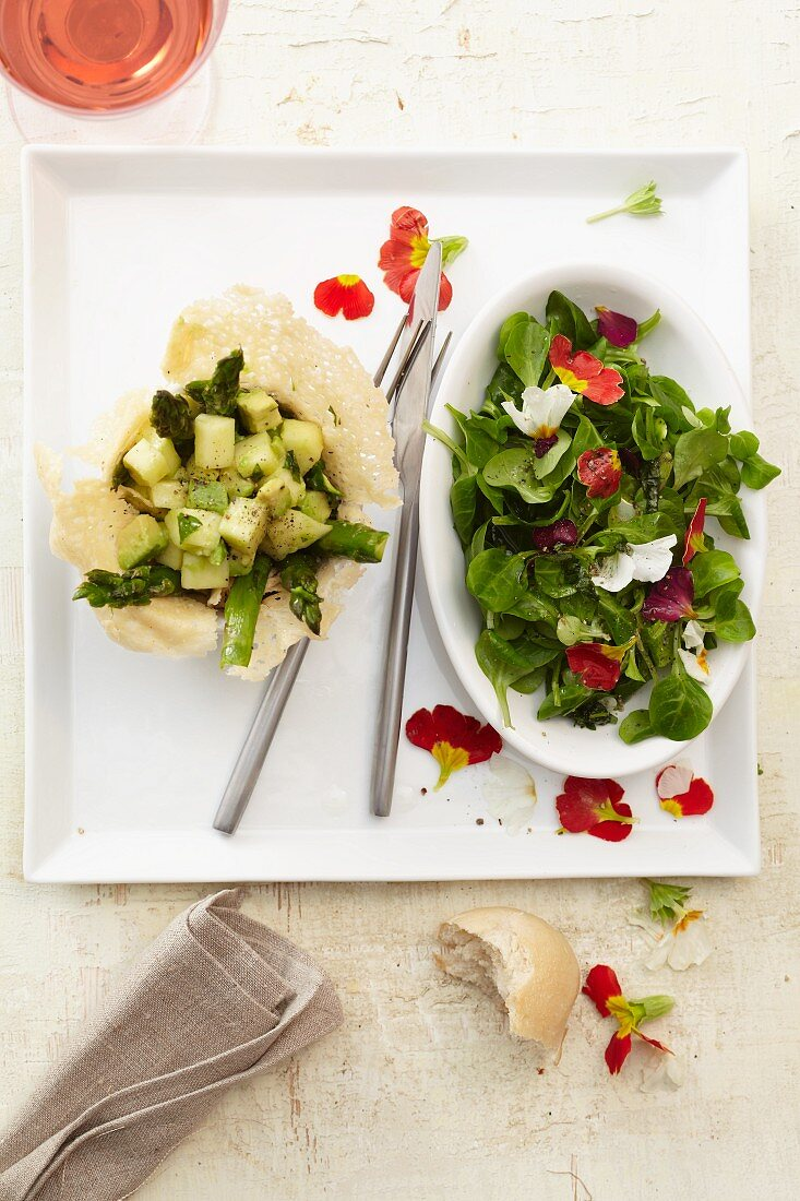 A parmesan bowl filled with avocado salad, and lamb's lettuce with primrose flowers