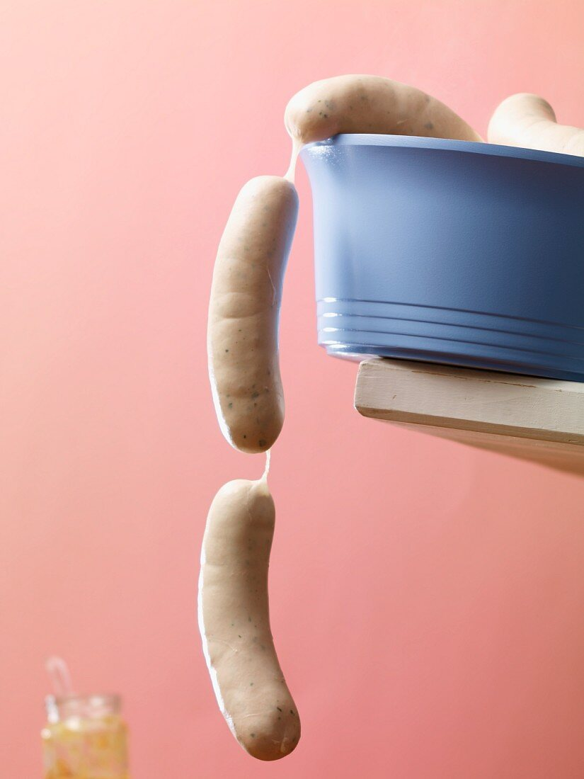 Raw white sausages hanging over the edge of a blue plastic bowl