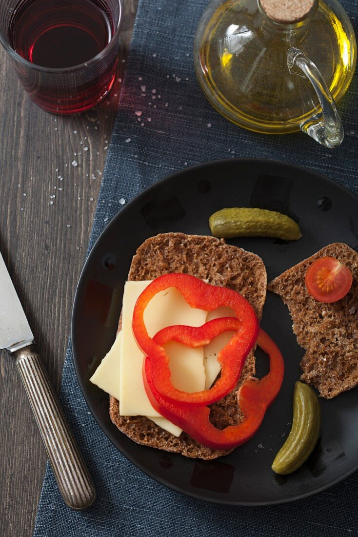 A slice of bread topped with cheese and peppers, with gherkins