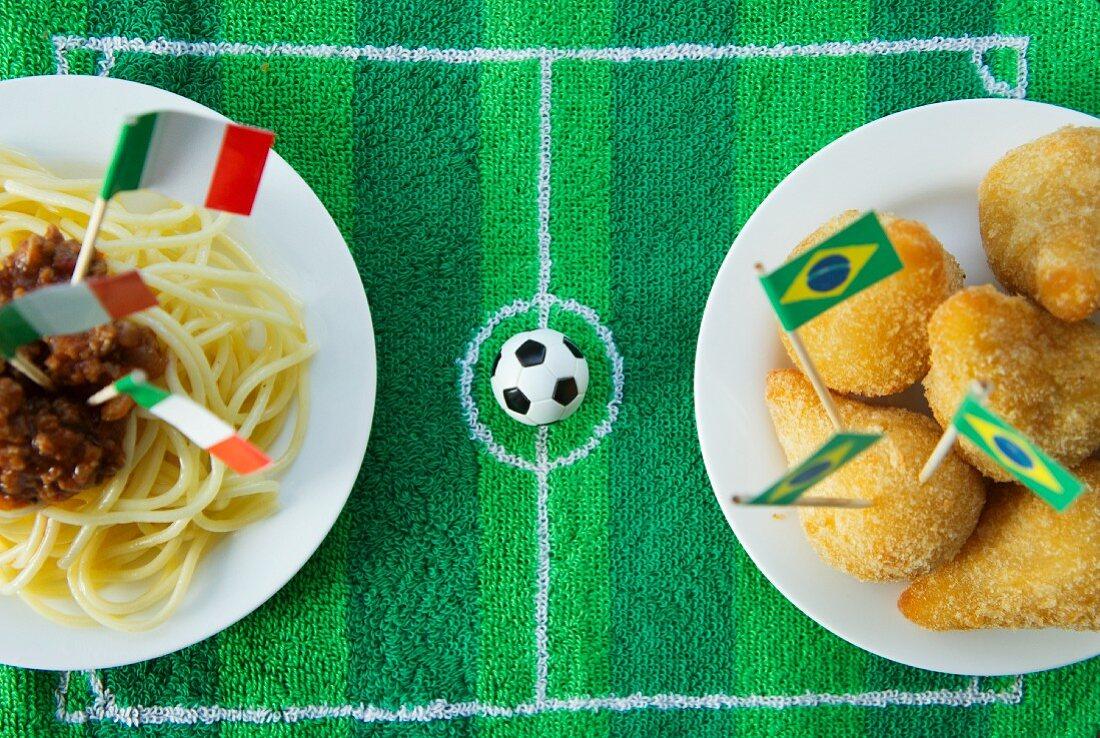 Spaghetti (Italy) and salgadinhos (Brazil) with football-themed decoration