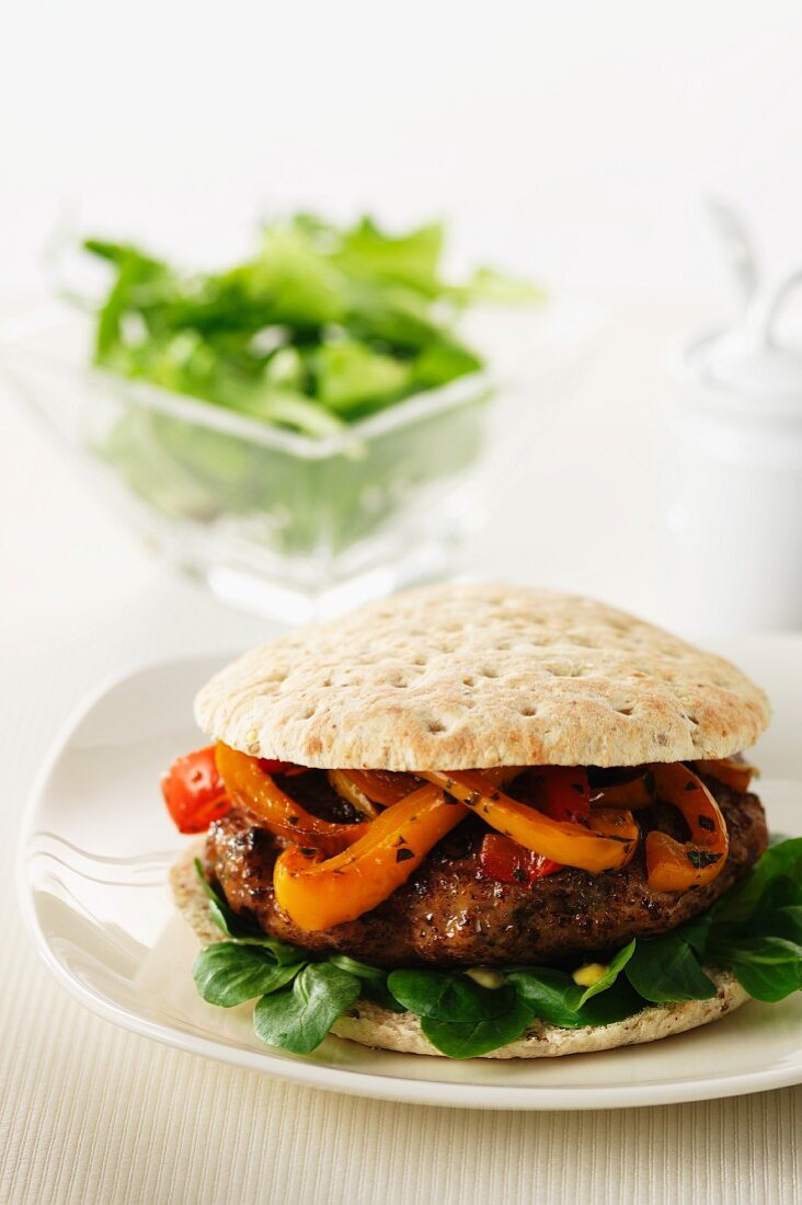 A burger in a multi-grain bun with strips of grilled pepper