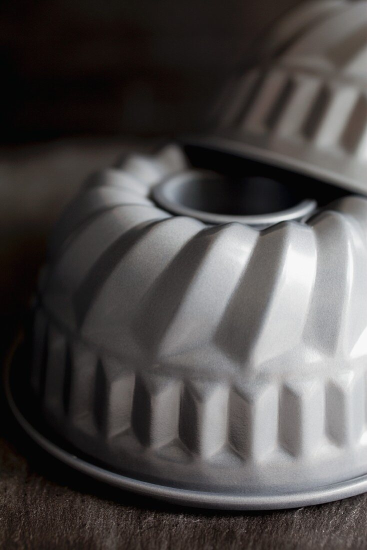 Two manature non-stick bundt ring cake tins against a black back