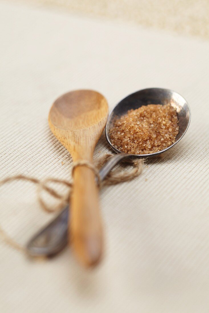 Wooden and Silver Spoon Tied Together; Raw Sugar in the Silver Spoon