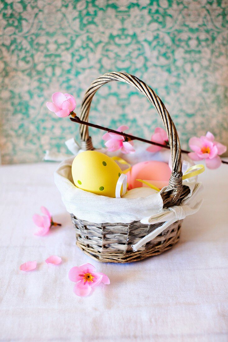 Eggs painted in pastel colours for Easter in a small basket