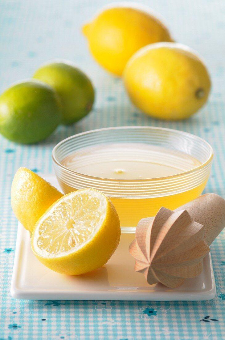 Lemon juice in a small dish, a lemon squeezer and citrus fruit