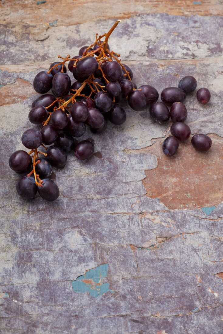Red grapes on a weathered surface