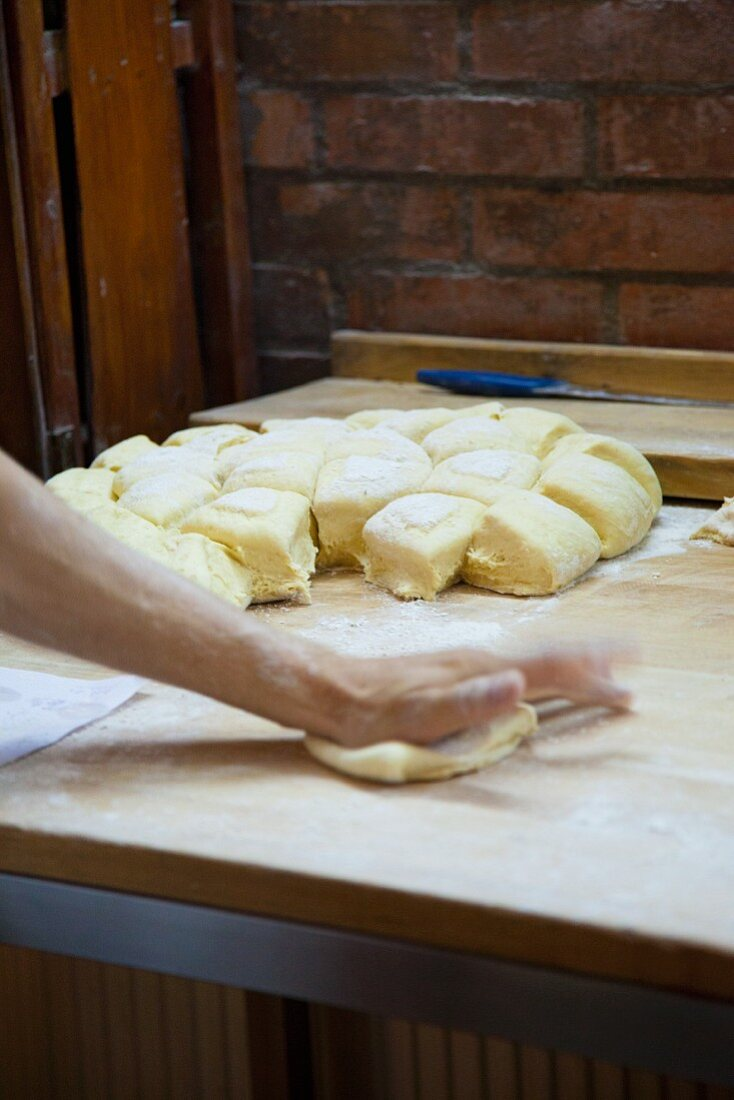 Hands shaping bread rolls in a bakery