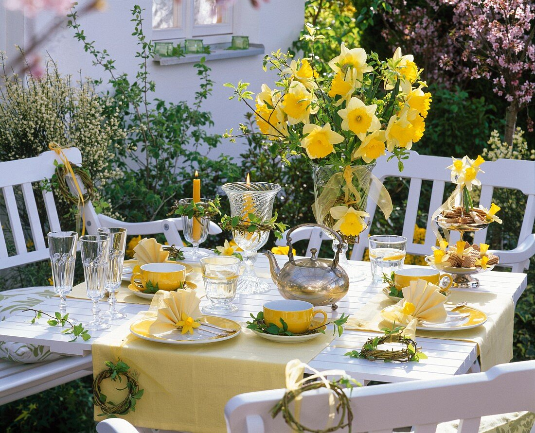 Yellow table decorations with serviettes folded into a fan shape, bouquet of narcissus and small willow wreaths