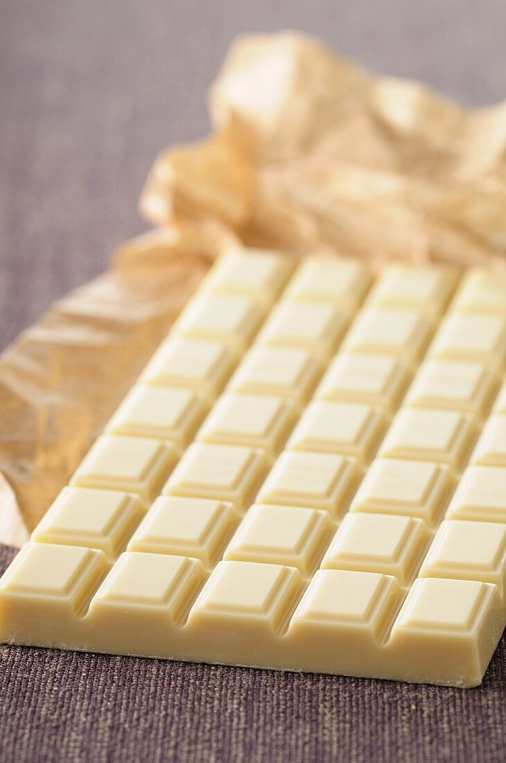 A bar of white chocolate with paper