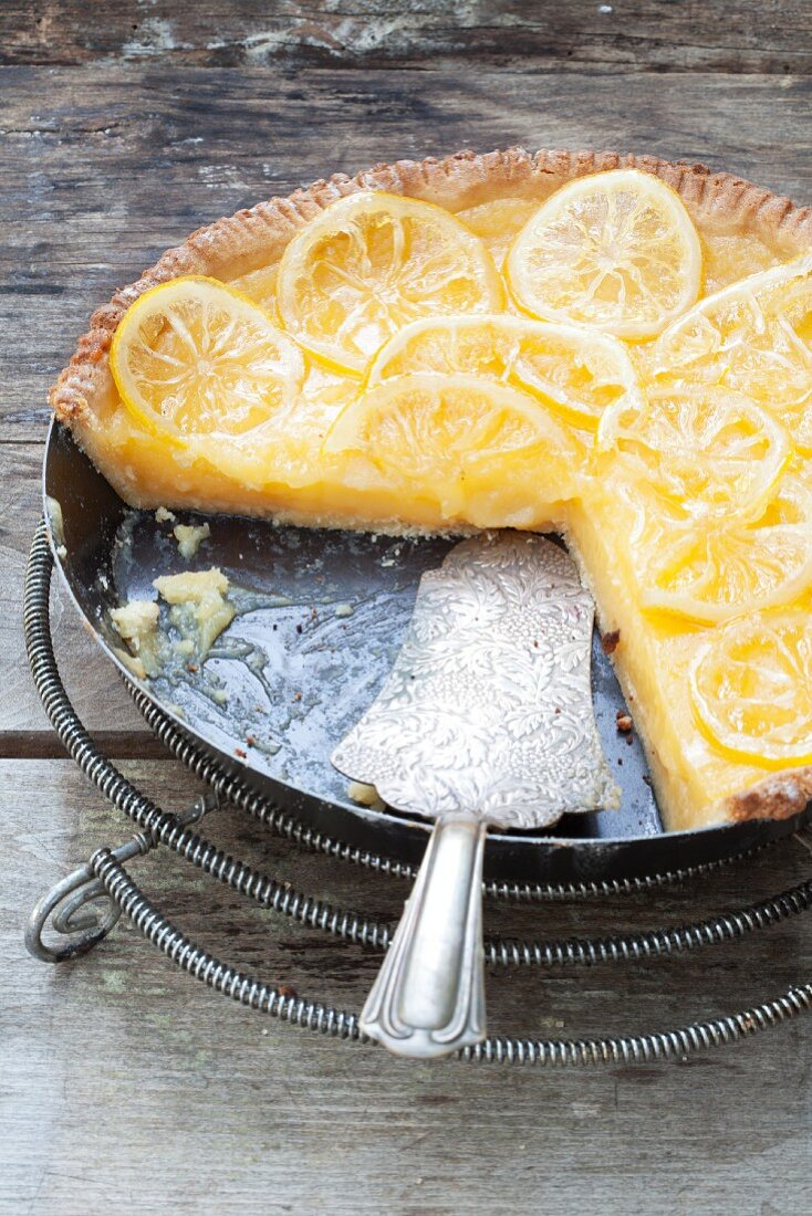 Lemon tart in a baking dish, partly sliced