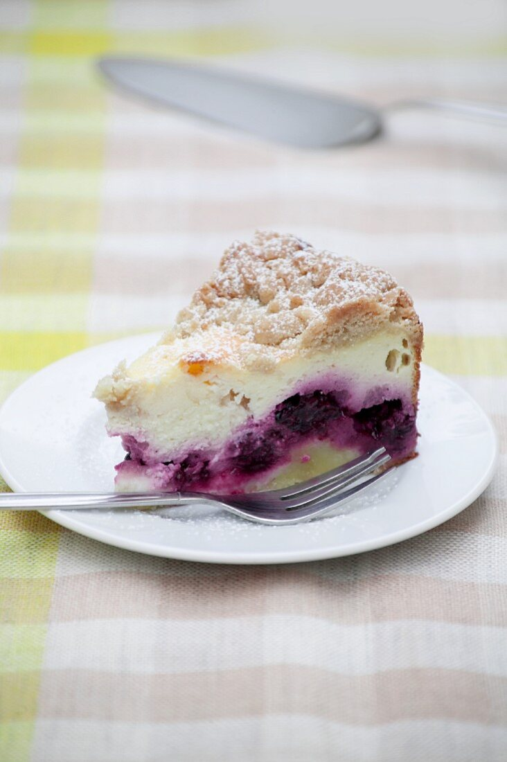 A slice of crumble-topped quark cake with blackberries