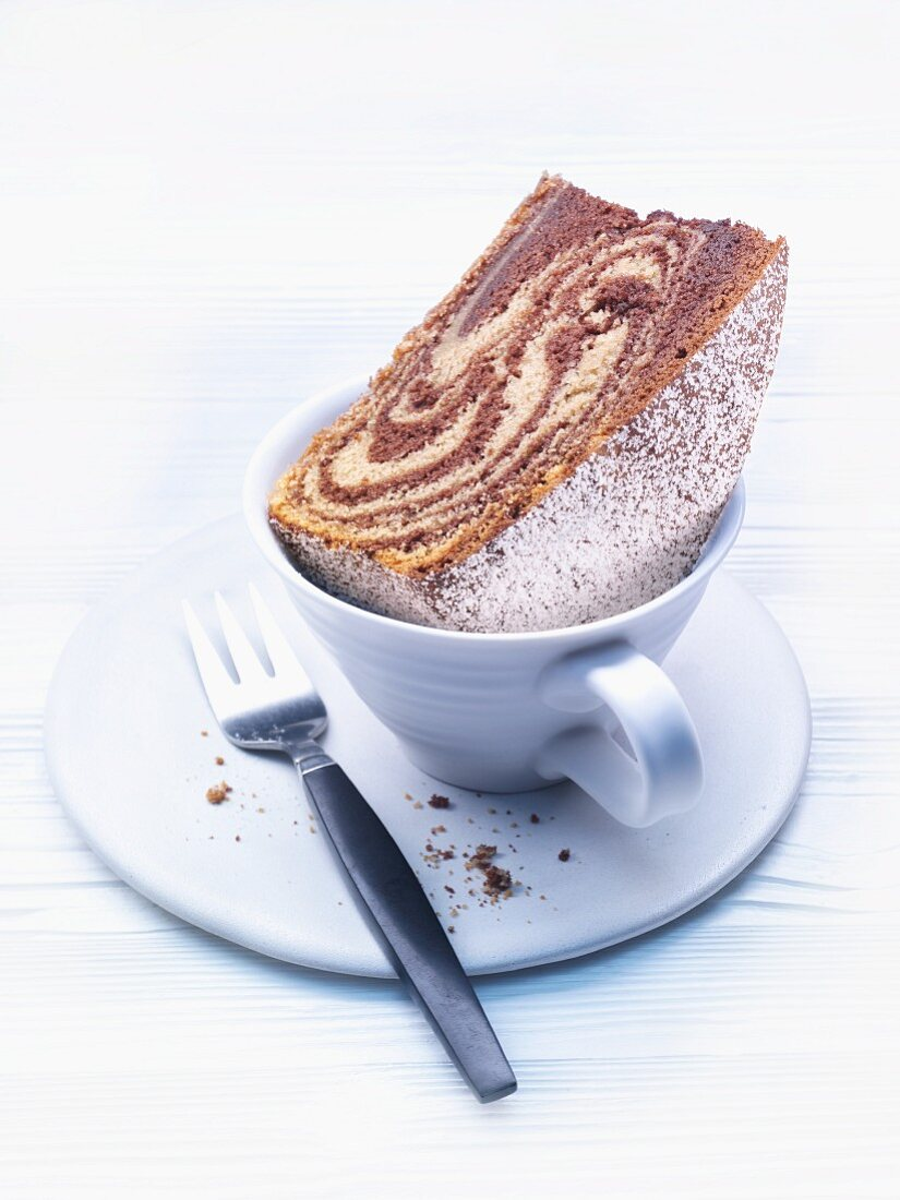 A slice of zebra cake in a coffee cup