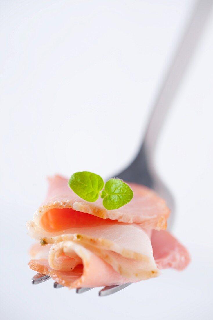 Sliced ham with an oregano leaf on a fork (close-up)