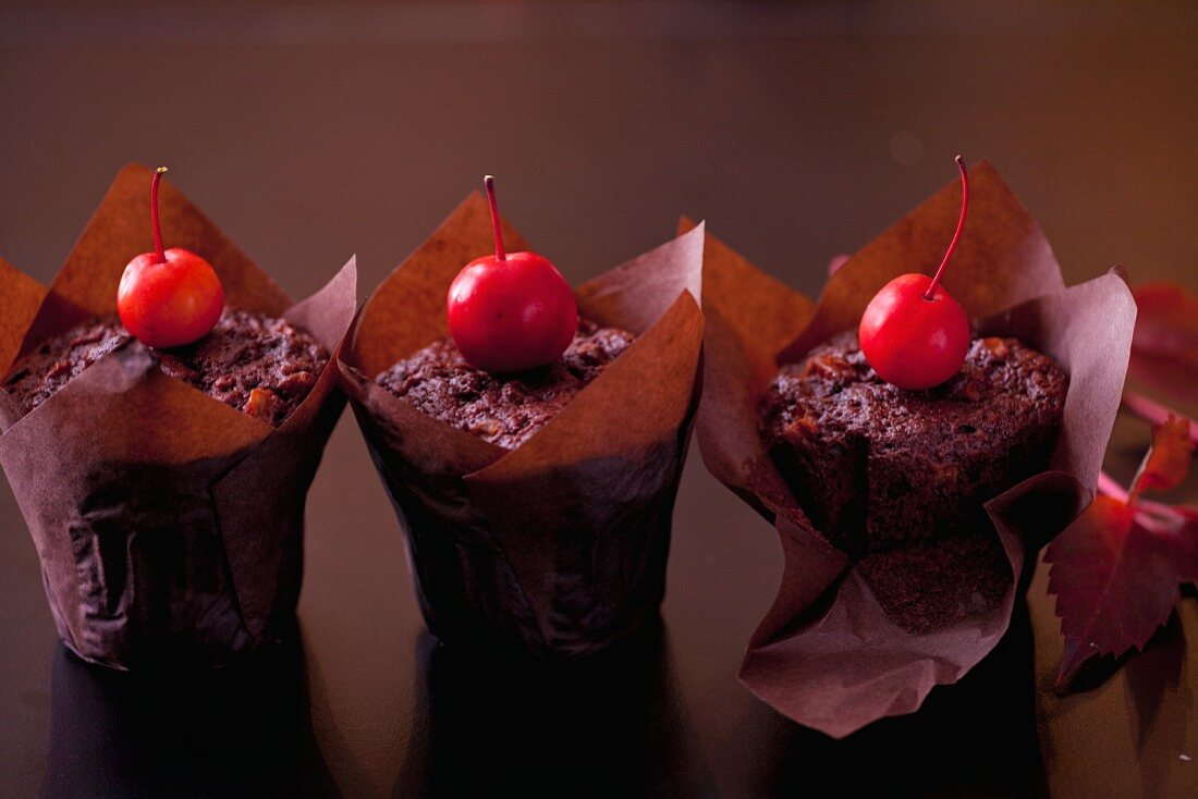 Chocolate and pear muffins garnished with whole cherry