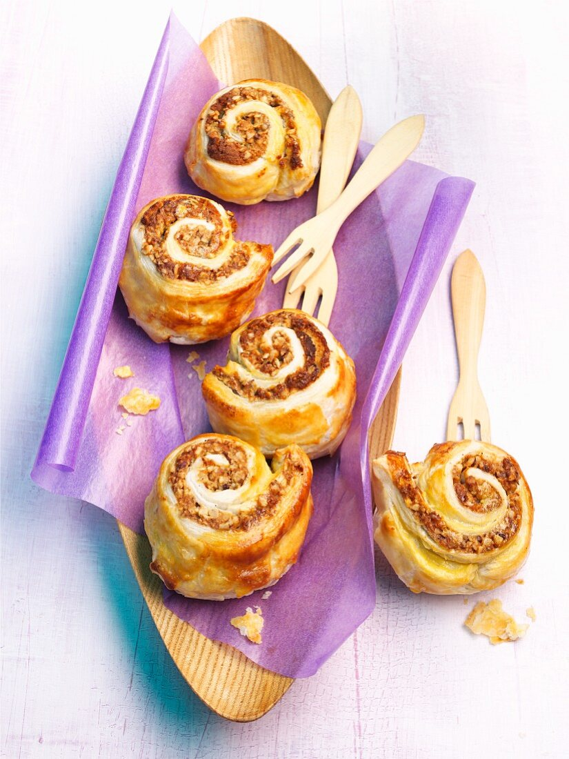Nut-filled pastry whirls on purple paper in a wooden dish