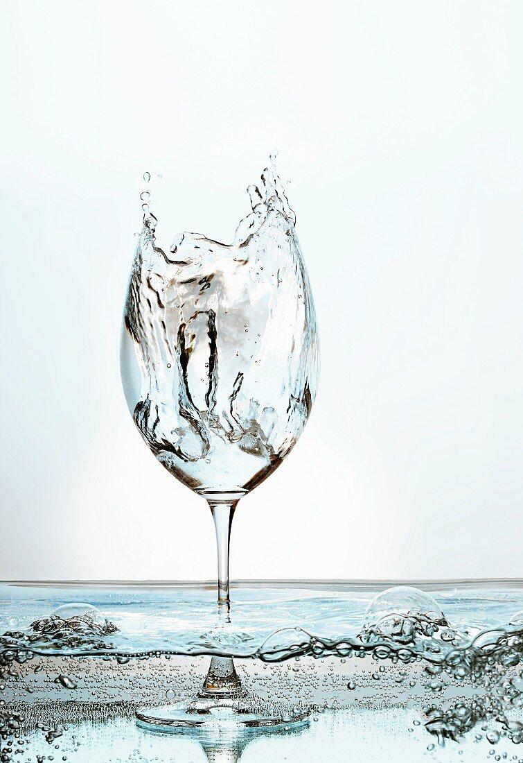 Mit spritzendem Wasser gefülltes Stielglas