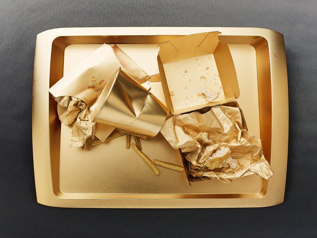 Reste eines Fast-Food-Menüs auf goldenem Tablett