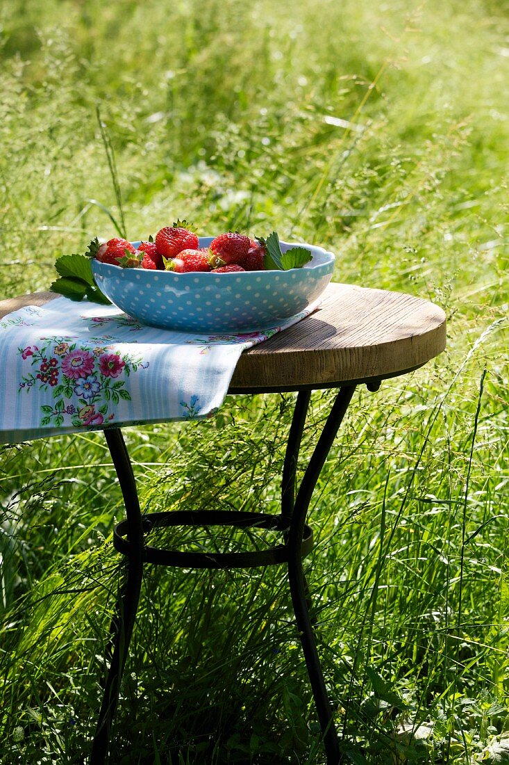 Strawberries in a bowl on a garden table
