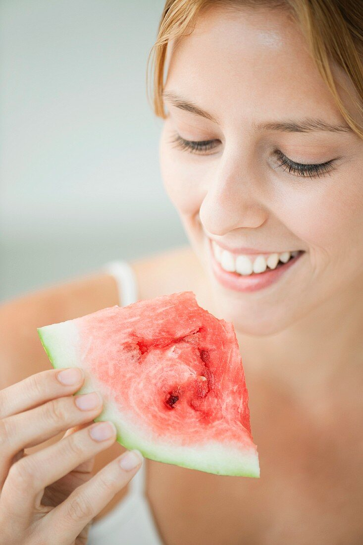 Young woman holding a slice of watermelon