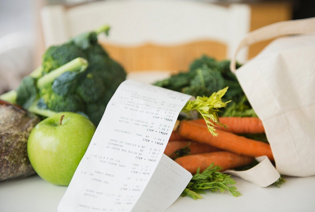 An apple and vegetables with shopping bag and receipt