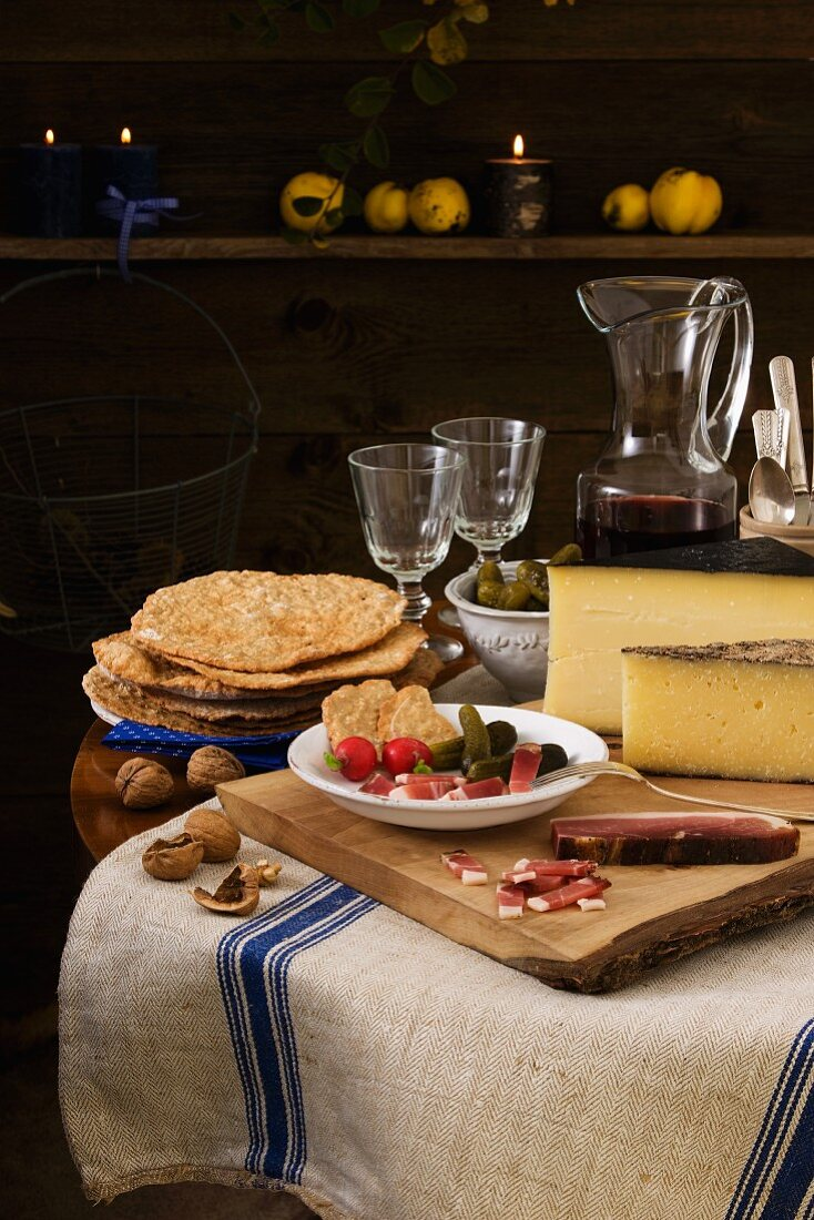 Rustic light meal from South Tyrol, consisting of dry-cured ham, Schüttelbrot (crispy unleavened bread), nuts, cheese and wine