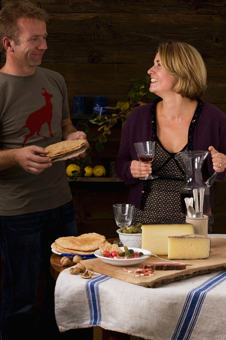 A couple eating a rustic South Tyrolean light meal with dry-cured ham, Schüttelbrot (crispy unleavened bread from South Tyrol), nuts, cheese and wine