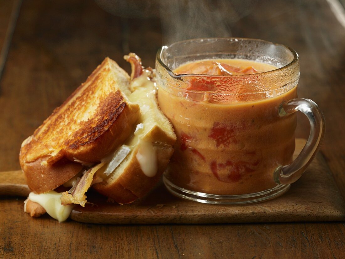 Half a Grilled Cheese and Bacon Sandwich with a Cup of Chunky Tomato Soup