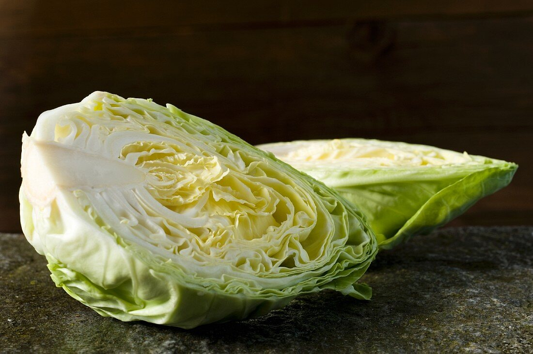 A pointed cabbage, halved, on a stone slab