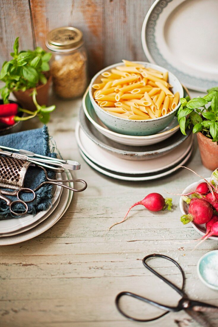 An arrangement of pasta, basil plants and kitchen utensils