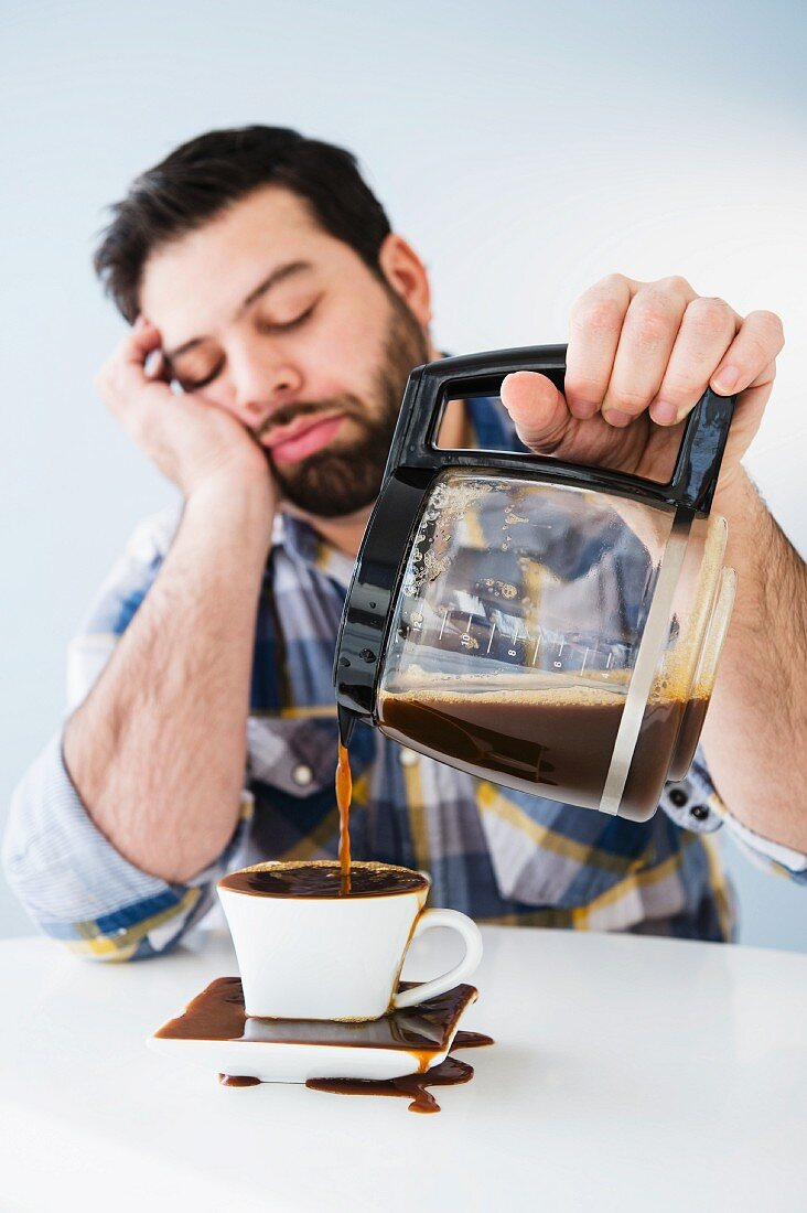 A man sitting at a table, almost fast asleep, spilling coffee