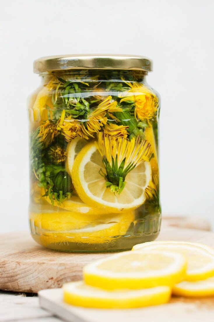 Jar of lemonade cordial made from dandelion flowers, lemons and sugar