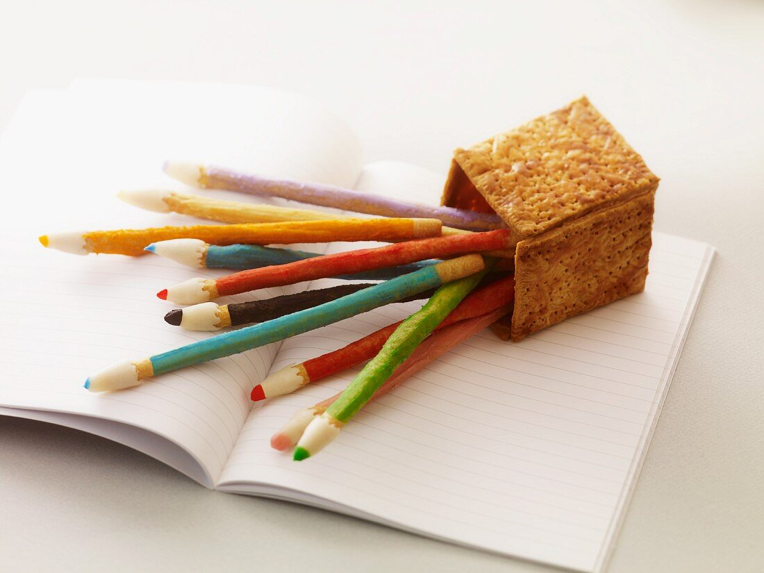 Edible colouring pencils with an edible pencil holder lying on a schoolbook