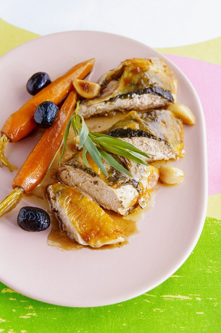 Guinea fowl stuffed under the skin and served with carrots, garlic and olives