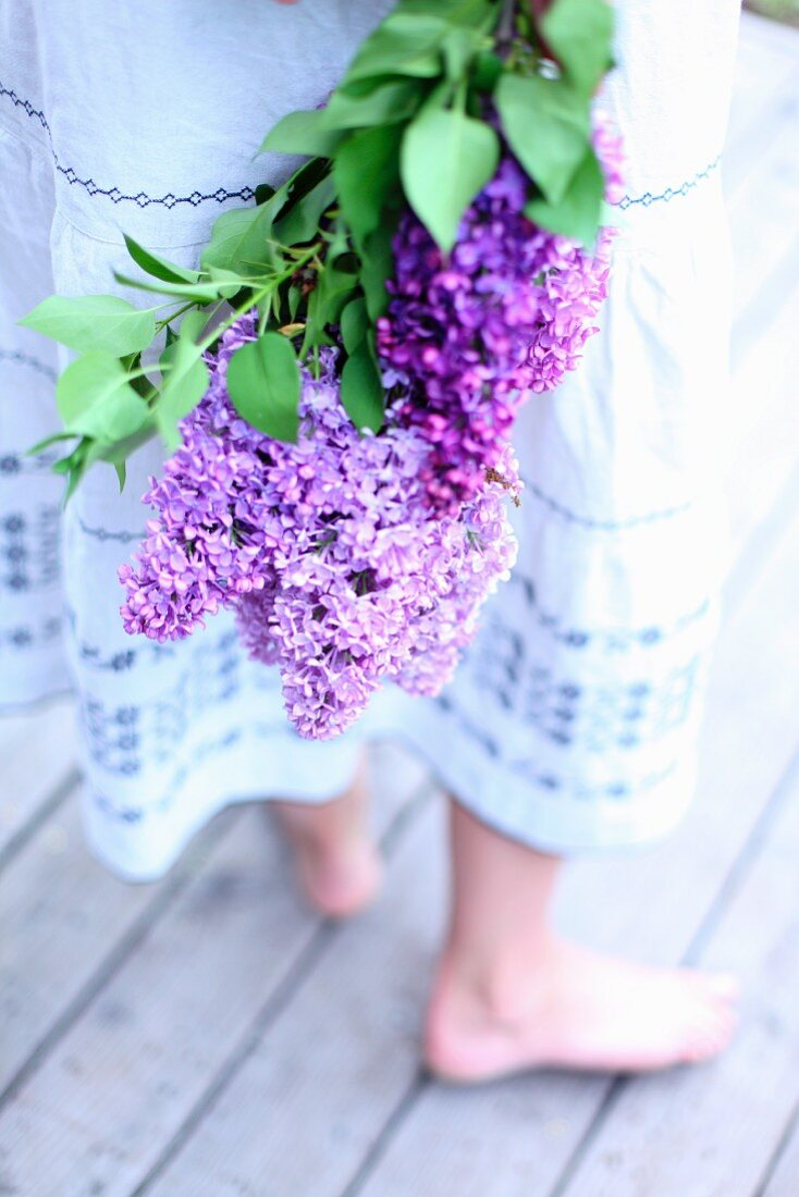 A young woman holding a bouquet of purple lilac flowers