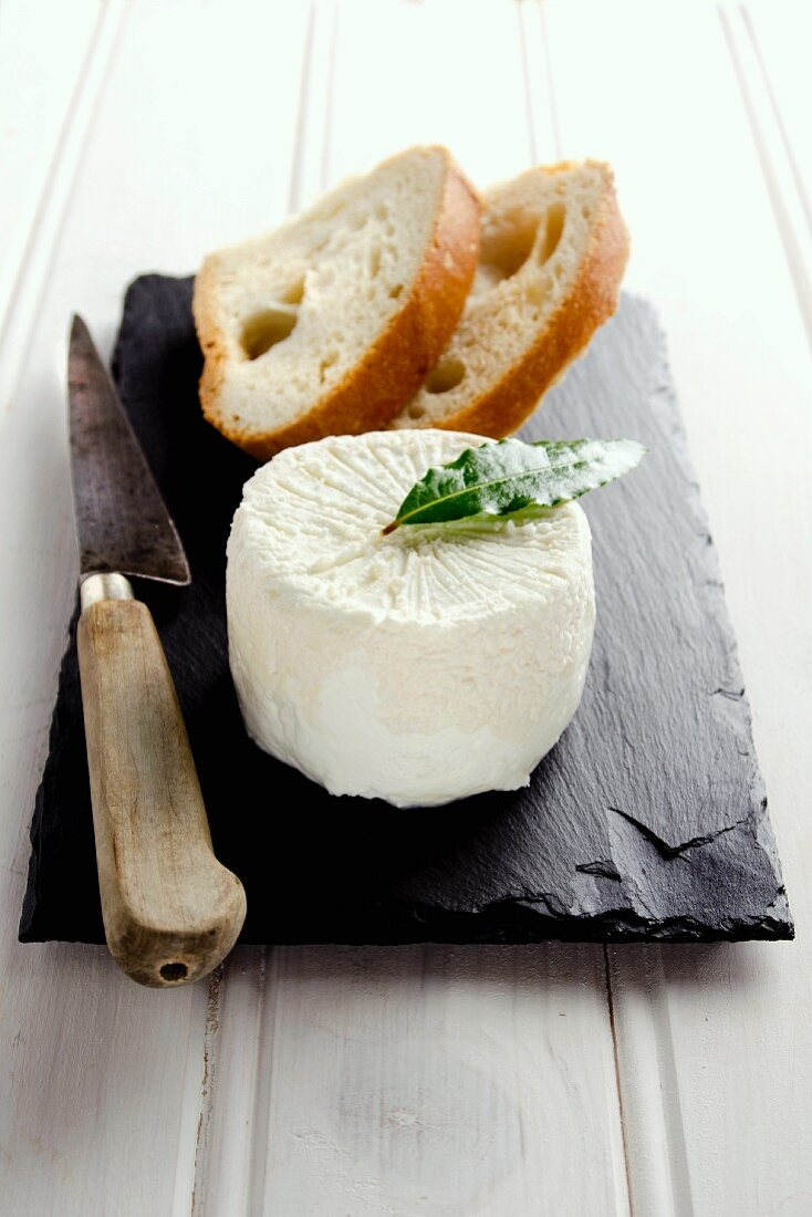 Goat's cheese on a slate slab with sliced bread