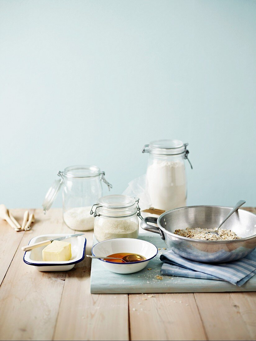 Biscuit ingredients in various jars and bowls, on a wooden tabletop