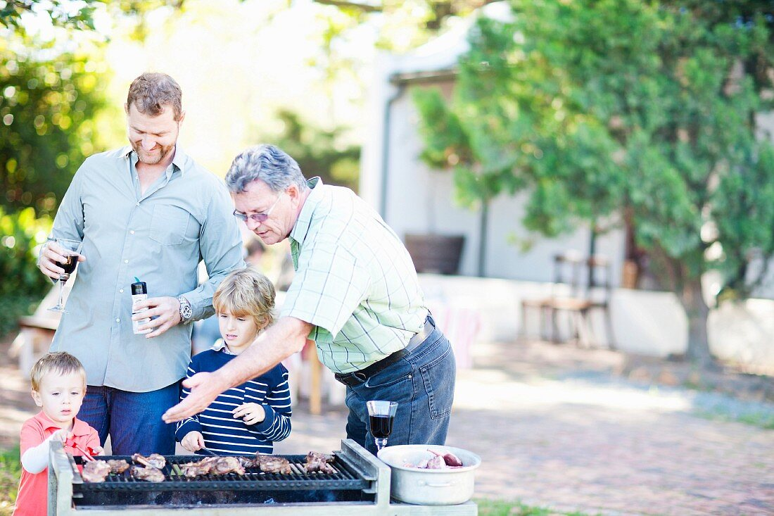 Men and boys barbecuing in the garden