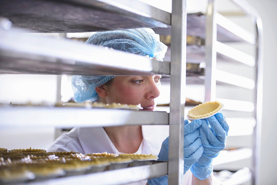 A baker checking freshly baked pie cases