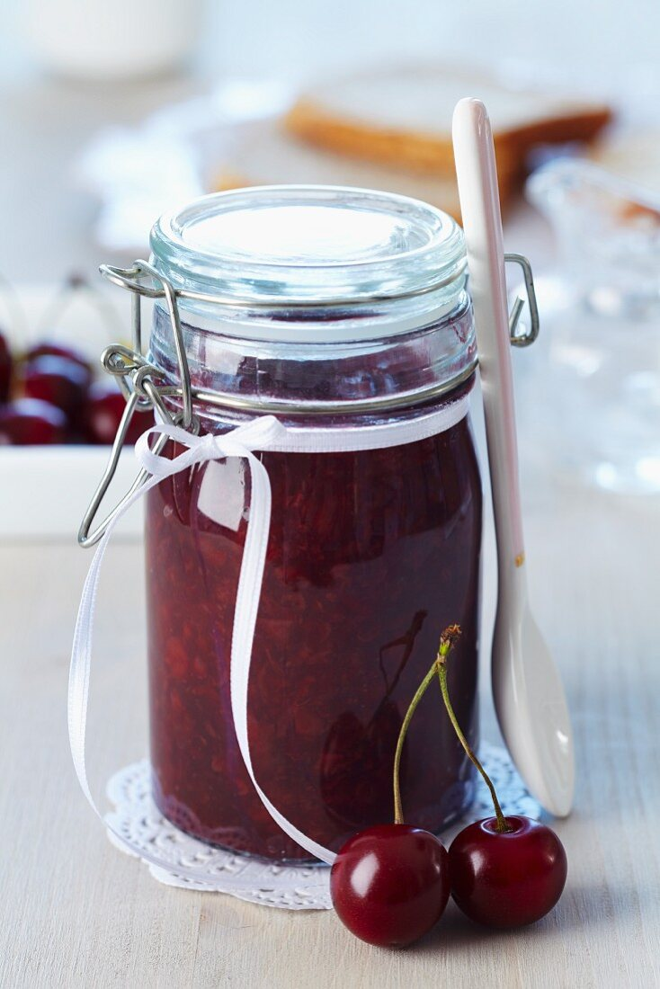 A jar of cherry jam decorated with a bow as a present