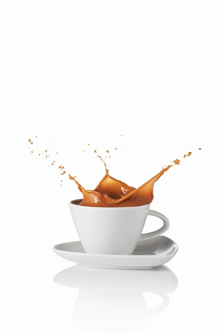 A latte splashing out of the cup