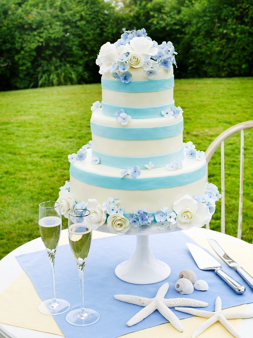 Blue and White Wedding Cake with Two Glasses of Champagne and Sea Shells on an Outdoor Table
