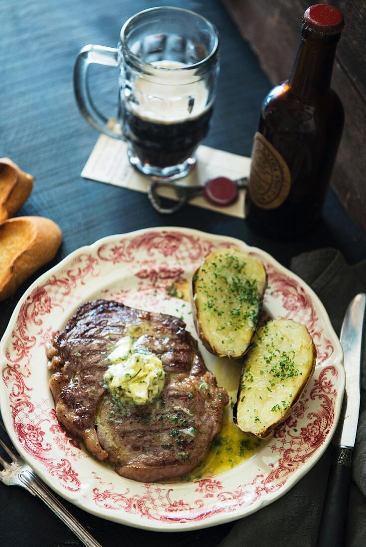 Beef steak with herb butter, potatoes and beer