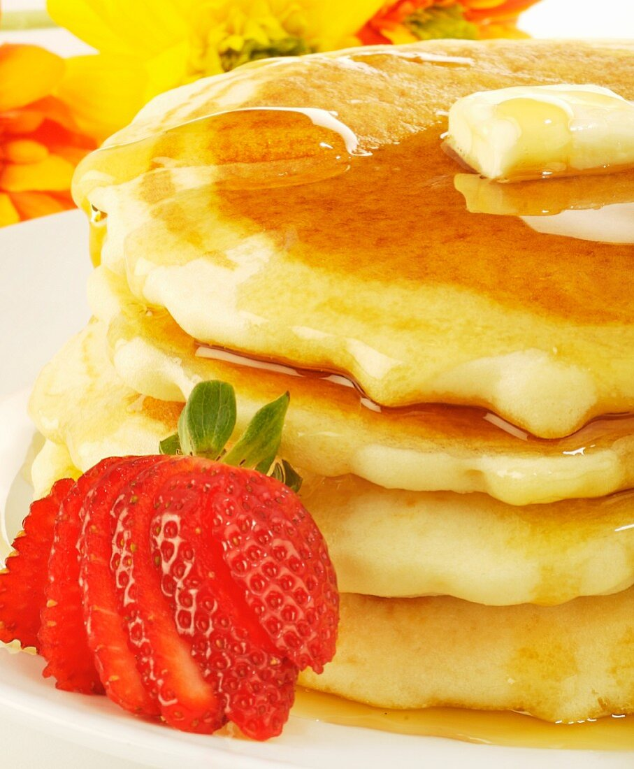 Stack of Pancakes with Butter and Maple Syrup; Strawberry