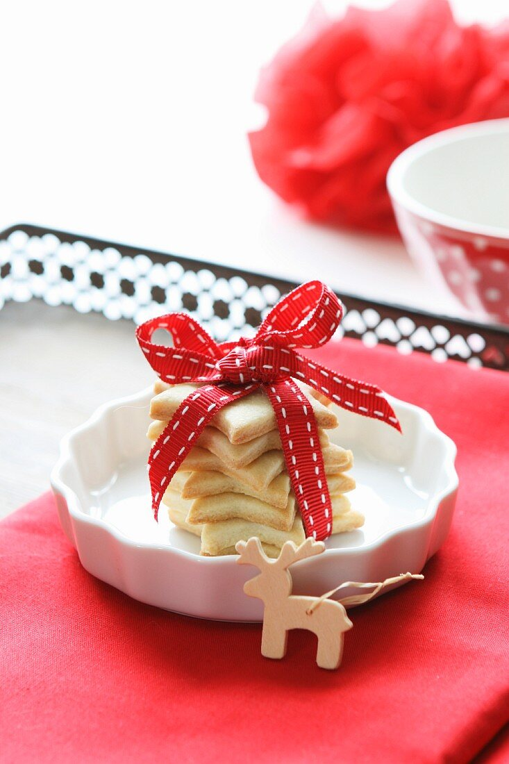 Star-shaped butter biscuits, wrapped and tied with a ribbon, with a wooden moose tree decoration