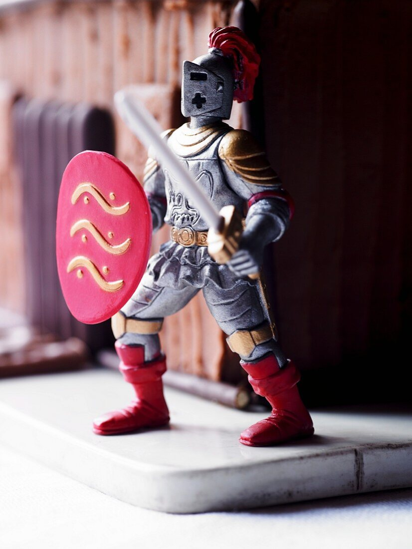 A knight figurine in front of a cake designed to look like a knight's castle