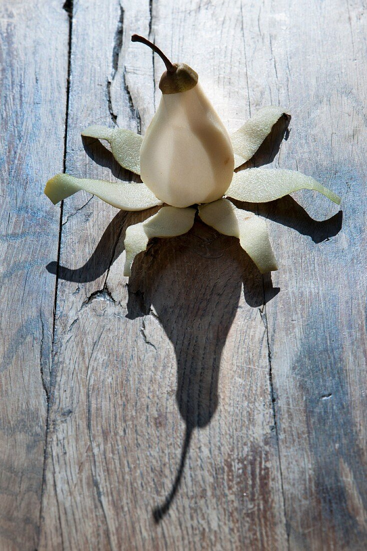 A peeled pear on a wooden surface