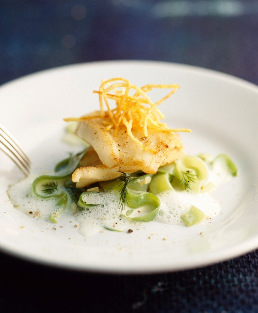 Fried fish fillets on cucumber strips with a dill foam