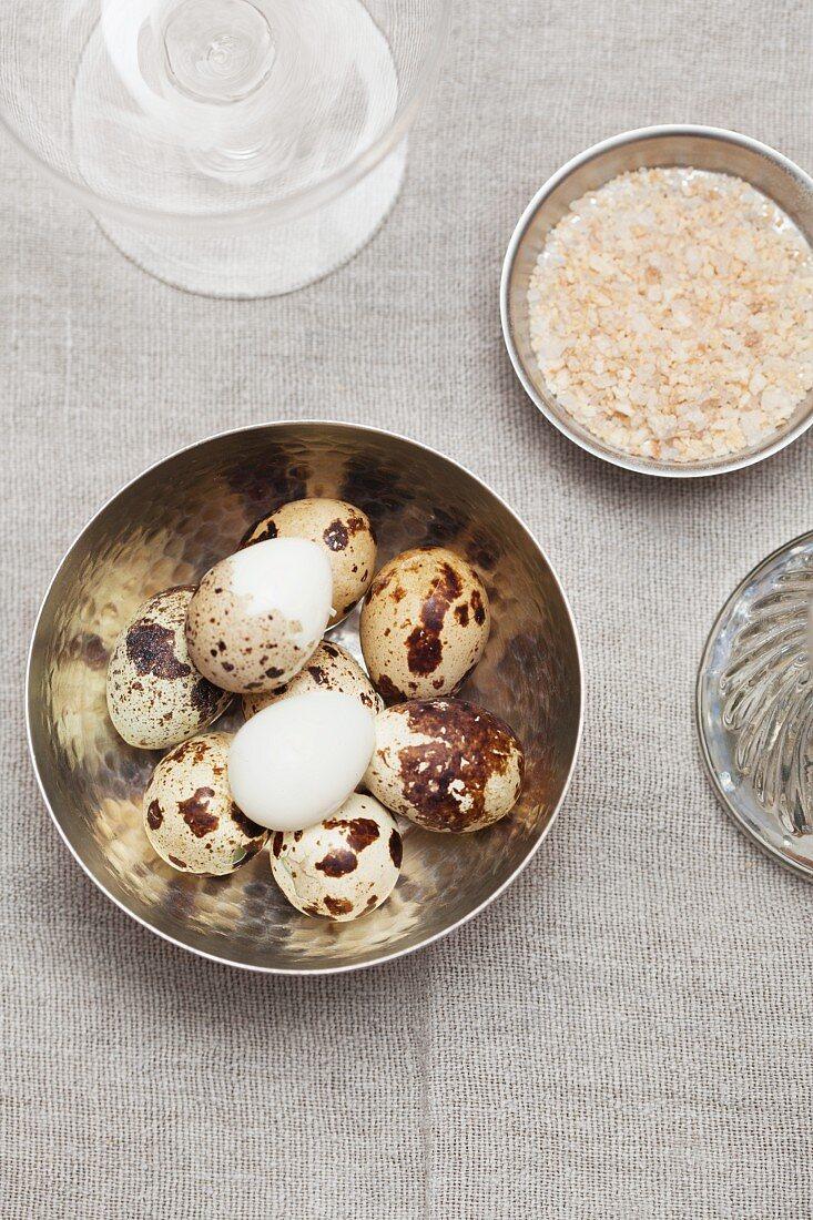 Boiled quail's eggs, partly peeled, with salt