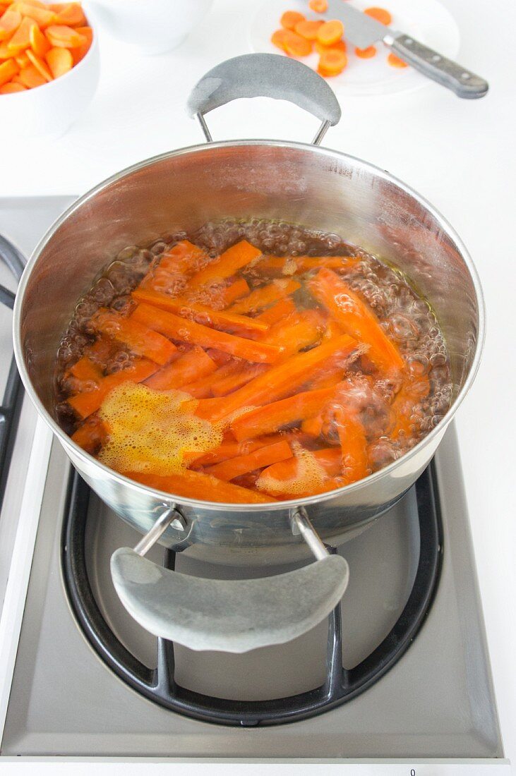 Carrots boiling on a gas hob