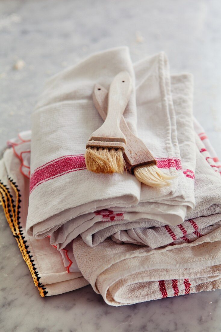 Two baking brushes on a stack of tea towels